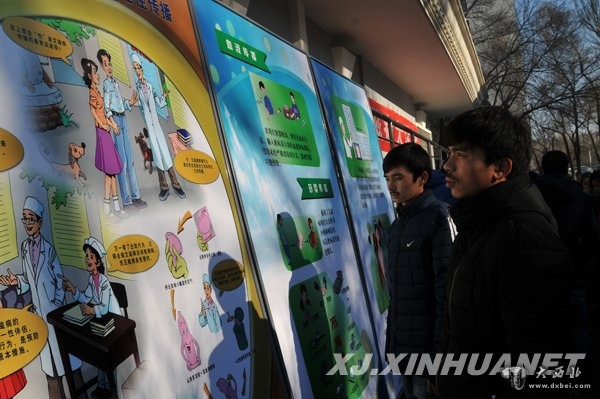新疆大学学生在观看预防艾滋病宣传展板